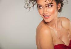 Προκλητική με μεγάλο στήθος γυναίκα στην κόκκινη δευτερεύουσα τοποθέτηση φορεμάτων Στοκ Φωτογραφίες
