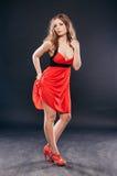 Προκλητική νέα γυναίκα ομορφιάς στο κόκκινο φόρεμα στοκ εικόνα