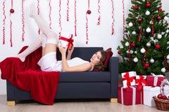 Προκλητική νέα γυναίκα που βρίσκεται στον καναπέ με το διακοσμημένο χριστουγεννιάτικο δέντρο Στοκ εικόνες με δικαίωμα ελεύθερης χρήσης
