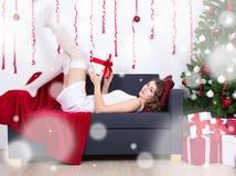 Προκλητική νέα γυναίκα που βρίσκεται στον καναπέ με το διακοσμημένο χριστουγεννιάτικο δέντρο Στοκ Φωτογραφία