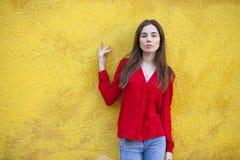 Προκλητική νέα γυναίκα, στα πλαίσια του κίτρινου τοίχου Στοκ Εικόνες