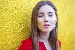 Προκλητική νέα γυναίκα, στα πλαίσια του κίτρινου τοίχου Στοκ φωτογραφία με δικαίωμα ελεύθερης χρήσης