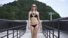 Προκλητική ξανθή γυναίκα γοητείας που φορά μαύρους swimwear και τα γυαλιά ηλίου που περπατά σε μια στέγη σε μια ηλιόλουστη θερινή φιλμ μικρού μήκους