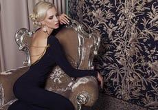 Προκλητική ξανθή γυναίκα γοητείας στο κομψό μαύρο φόρεμα Στοκ Φωτογραφίες