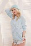 Προκλητική ξανθή γυναίκα που φορά το πουλόβερ και το καπέλο σορτς Στοκ Εικόνες