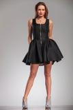 Προκλητική ξανθή γυναίκα στο μαύρο φόρεμα και τα υψηλά παπούτσια τακουνιών Στοκ Φωτογραφίες