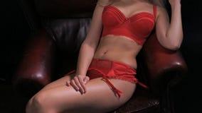 Προκλητική συνεδρίαση γυναικών στην πολυθρόνα που φορά lingerie απόθεμα βίντεο