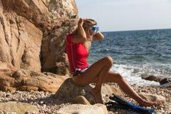 Προκλητική συνεδρίαση κοριτσιών δυτών στον απότομο βράχο της δύσκολων παραλίας και της προετοιμασίας Στοκ Φωτογραφίες