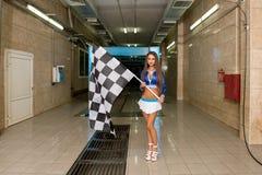 Προκλητική τοποθέτηση γυναικών με την ελεγμένη σημαία στο πλύσιμο αυτοκινήτων Στοκ Εικόνες