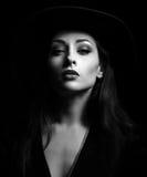 Προκλητική τοποθέτηση γυναικών makeup γοητείας στο καπέλο μόδας στο σκοτεινό backgrou στοκ φωτογραφία