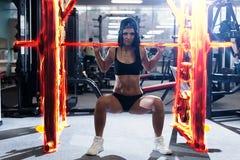 Προκλητική φίλαθλη γυναίκα που κάνει την άσκηση ικανότητας δύναμης στην αθλητική γυμναστική Όμορφο κορίτσι που επιλύει στη γυμνασ στοκ εικόνα