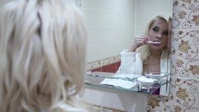 Προκλητική blondy γυναίκα που βουρτσίζει τα δόντια της στον καθρέφτη αντανάκλασης λουτρών φιλμ μικρού μήκους