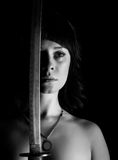 Προκλητική nude γυναίκα κινηματογραφήσεων σε πρώτο πλάνο με το ξίφος στο σκοτεινό υπόβαθρο μαύρο λευκό Στοκ φωτογραφία με δικαίωμα ελεύθερης χρήσης