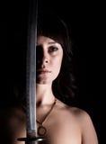 Προκλητική nude γυναίκα κινηματογραφήσεων σε πρώτο πλάνο με το ξίφος στο σκοτεινό υπόβαθρο Στοκ Φωτογραφίες
