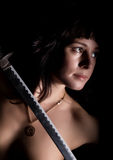 Προκλητική nude γυναίκα κινηματογραφήσεων σε πρώτο πλάνο με το ξίφος στο σκοτεινό υπόβαθρο Στοκ φωτογραφία με δικαίωμα ελεύθερης χρήσης