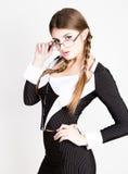 Προκλητικός γραμματέας, πορτρέτο της όμορφης επιχειρησιακής κυρίας brunette που φορά στο ριγωτό κοστούμι που δαγκώνει τη λαβή των Στοκ Φωτογραφίες