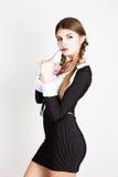 Προκλητικός γραμματέας, πορτρέτο της όμορφης επιχειρησιακής κυρίας brunette που φορά στο ριγωτό κοστούμι που δαγκώνει τη λαβή των Στοκ φωτογραφίες με δικαίωμα ελεύθερης χρήσης