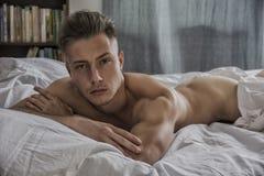 Προκλητικός γυμνός νεαρός άνδρας στο κρεβάτι στοκ εικόνα