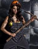 Προκλητικός εργαζόμενος ανθρακωρύχων θηλυκών με την αξίνα, στις φόρμες πέρα από το γυμνό σώμα του Στοκ Εικόνες