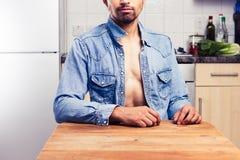 Προκλητικός νεαρός άνδρας στην κουζίνα Στοκ Εικόνες