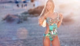 Προκλητικός ξανθός σε ένα μοντέρνο μαγιό στο ηλιοβασίλεμα Στοκ Εικόνες