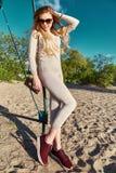 Προκλητικός περίπατος γυναικών στο knitwear ένδυσης παραλιών άμμων κοστούμι Στοκ Φωτογραφίες