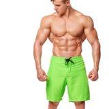 Προκλητικό αθλητικό άτομο που παρουσιάζει το μυϊκά σώμα και sixpack ABS, που απομονώνονται πέρα από το άσπρο υπόβαθρο Το ισχυρό α Στοκ φωτογραφίες με δικαίωμα ελεύθερης χρήσης