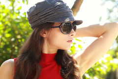 Προκλητικό θηλυκό πρότυπο στα γυαλιά ήλιων που θέτουν υπαίθρια Στοκ Εικόνες