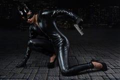 Προκλητικό θηλυκό στο μαύρο catwoman κοστούμι στοκ εικόνα