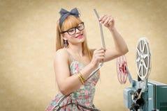 Προκλητικό καρφίτσα-επάνω κορίτσι με το εξέλικτρο ταινιών και τον εκλεκτής ποιότητας προβολέα Στοκ εικόνα με δικαίωμα ελεύθερης χρήσης