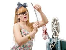Προκλητικό καρφίτσα-επάνω κορίτσι με το εξέλικτρο ταινιών και τον εκλεκτής ποιότητας προβολέα Στοκ Εικόνα