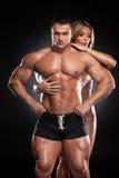 Προκλητικό κατάλληλο ξανθό κορίτσι που αγκαλιάζει από το πίσω αρσενικό bodybuilder. Στοκ εικόνα με δικαίωμα ελεύθερης χρήσης