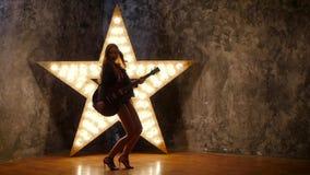 Προκλητικό κορίτσι βράχου που χορεύει με την ηλεκτρική κιθάρα φιλμ μικρού μήκους