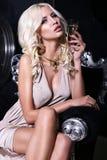 Προκλητικό κορίτσι με τα ξανθά μαλλιά με το ποτήρι της σαμπάνιας Στοκ Εικόνες