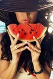 Προκλητικό κορίτσι με τη σκοτεινή τρίχα που τρώει το καρπούζι στοκ φωτογραφία με δικαίωμα ελεύθερης χρήσης