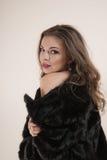 Προκλητικό κορίτσι ξανθό στη μαύρη γούνα Στοκ Εικόνες