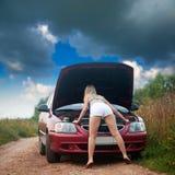 Προκλητικό κορίτσι που κοιτάζει κάτω από την κουκούλα αυτοκινήτων στοκ φωτογραφίες