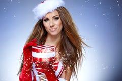 Προκλητικό κορίτσι που φορά τα ενδύματα Άγιου Βασίλη με τα Χριστούγεννα γ Στοκ Φωτογραφία