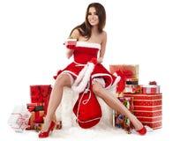 προκλητικό κορίτσι που φορά τα ενδύματα Άγιου Βασίλη με τα Χριστούγεννα γ Στοκ Φωτογραφίες