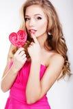 Προκλητικό κορίτσι που φορά το ρόδινο φόρεμα με την καραμέλα. Στοκ Φωτογραφίες