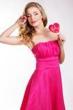 Προκλητικό κορίτσι που φορά το ρόδινο φόρεμα με την καραμέλα. Στοκ Εικόνα