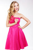 Προκλητικό κορίτσι που φορά το ρόδινο φόρεμα με την καραμέλα. Στοκ Φωτογραφία
