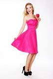 Προκλητικό κορίτσι που φορά το ρόδινο φόρεμα με την καραμέλα. Στοκ Εικόνες