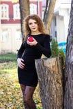 Προκλητικό κορίτσι σε ένα μαύρο φόρεμα με το κόκκινο μήλο Στοκ φωτογραφία με δικαίωμα ελεύθερης χρήσης