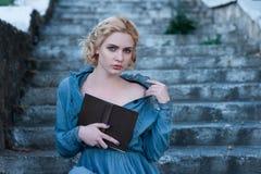 Προκλητικό κορίτσι σε μια εκλεκτής ποιότητας συνεδρίαση φορεμάτων με ένα βιβλίο στα σκαλοπάτια Στοκ Φωτογραφία