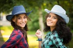 Προκλητικό κορίτσι στα καπέλα κάουμποϋ και τα πουκάμισα καρό στοκ εικόνες