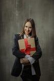 Προκλητικό κορίτσι στο κλασικό σακάκι και πουκάμισο με ένα δώρο στα χέρια s Στοκ εικόνα με δικαίωμα ελεύθερης χρήσης