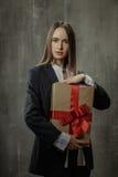 Προκλητικό κορίτσι στο κλασικό σακάκι και πουκάμισο με ένα δώρο στα χέρια s Στοκ εικόνες με δικαίωμα ελεύθερης χρήσης