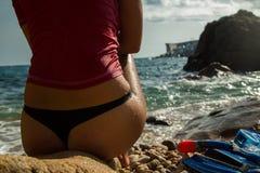 Προκλητικό κορίτσι sportswear και tanga στη συνεδρίαση σειράς στον απότομο βράχο Στοκ Φωτογραφία