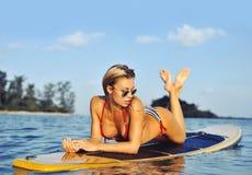 Προκλητικό κορίτσι surfer που βρίσκεται σε μια ιστιοσανίδα στη θάλασσα Στοκ Φωτογραφίες